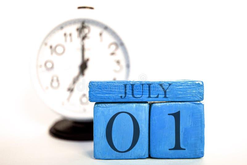 7月1日天1月、手工制造木日历和闹钟在蓝色 夏天月,年概念的天 免版税库存照片