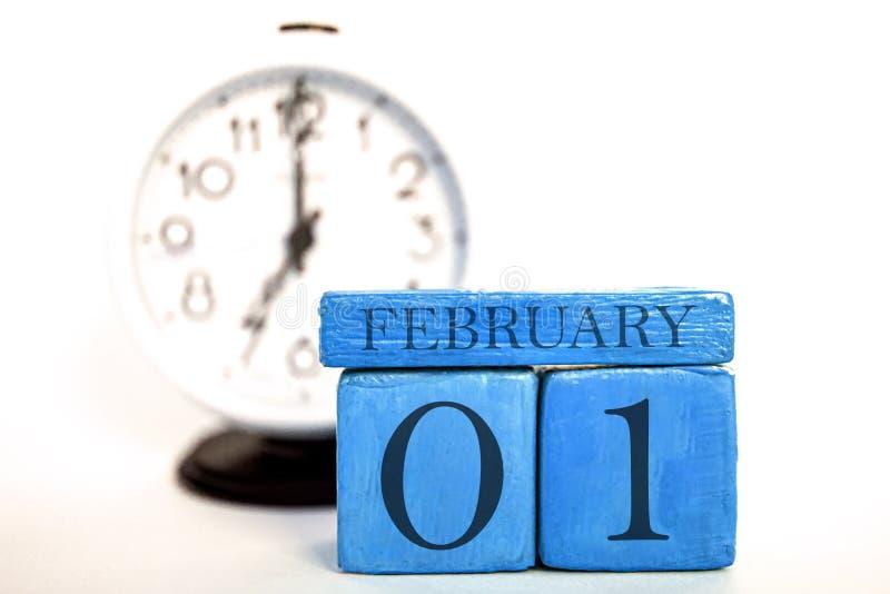 2月1日天1月、手工制造木日历和闹钟在蓝色 E 免版税库存照片