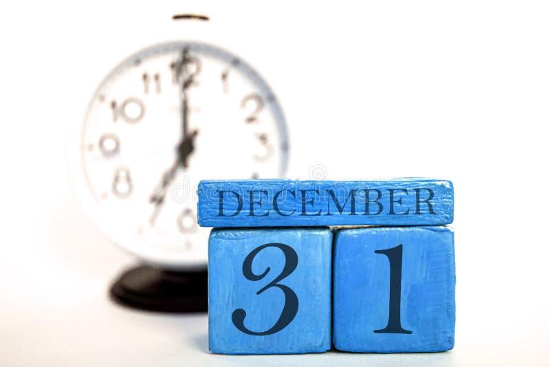 12月31日天31of月、手工制造木日历和闹钟在蓝色 E 免版税库存图片