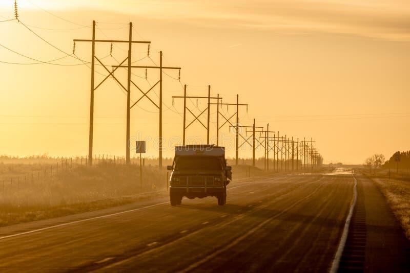2017年3月8日,内布拉斯加-在农村农厂乡下公路的日落有驾驶由输电线行的卡车的  免版税图库摄影