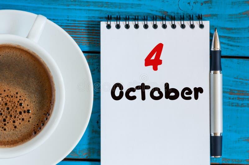 10月4日 在作业簿的天4月,日历用茶或在学生工作场所背景的咖啡杯 秋天时间 免版税图库摄影