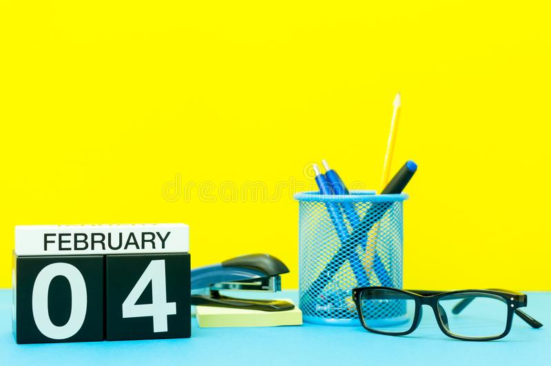 2月4日 天4 2月月,在黄色背景的日历与办公用品 花雪时间冬天 免版税库存照片
