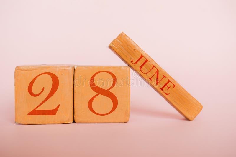 6月28日 天28月,在现代颜色背景的手工制造木日历 夏天月,年概念的天 免版税库存图片