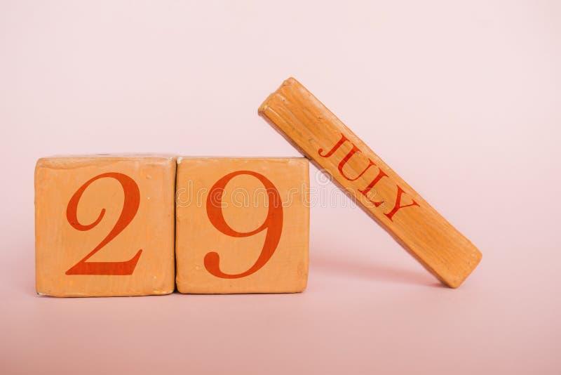 7月29日 天29月,在现代颜色背景的手工制造木日历 夏天月,年概念的天 免版税库存照片