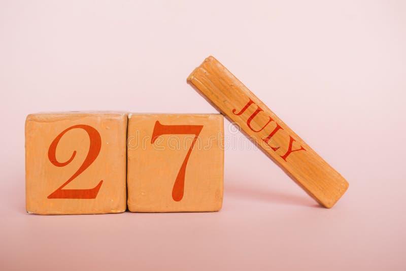7月27日 天27月,在现代颜色背景的手工制造木日历 夏天月,年概念的天 免版税库存图片