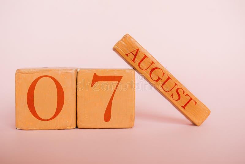 8月7日 天7月,在现代颜色背景的手工制造木日历 夏天月,年概念的天 库存图片