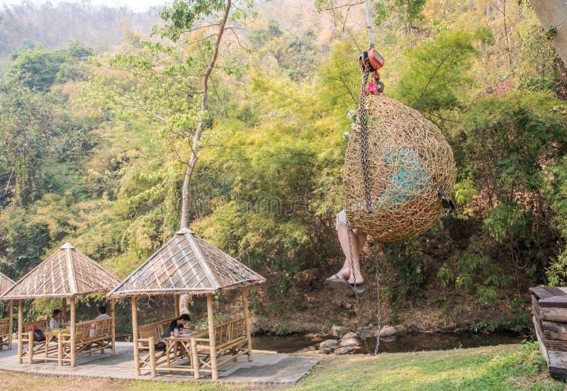 3月1日CHIANGMAI泰国:人们在山区度假村需要假期,垂悬在藤条摇摆和休闲在小小河旁边 库存图片