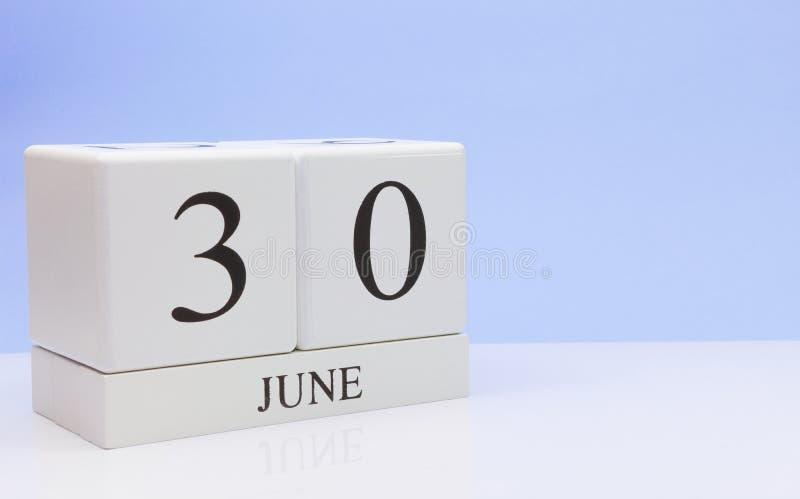 6月30st日天30月,在白色桌上的日历与反射,有浅兰的背景 夏时,空的空间 免版税库存照片
