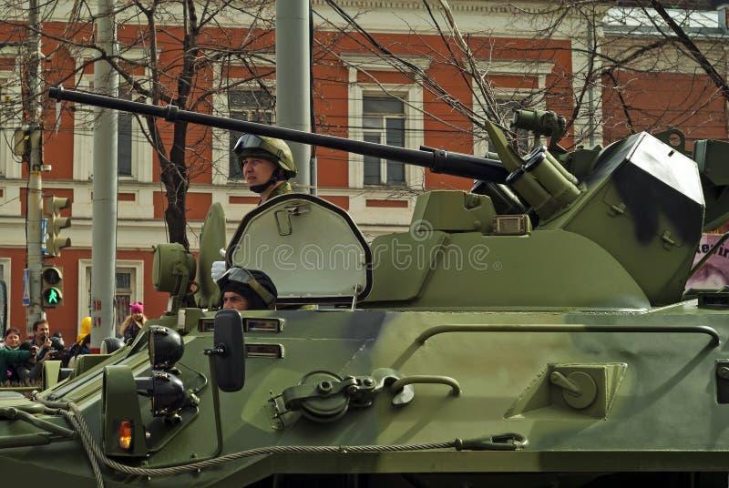 有一个乘员组的装甲运兵车在胜利天游行以后的一条城市街道上 库存图片