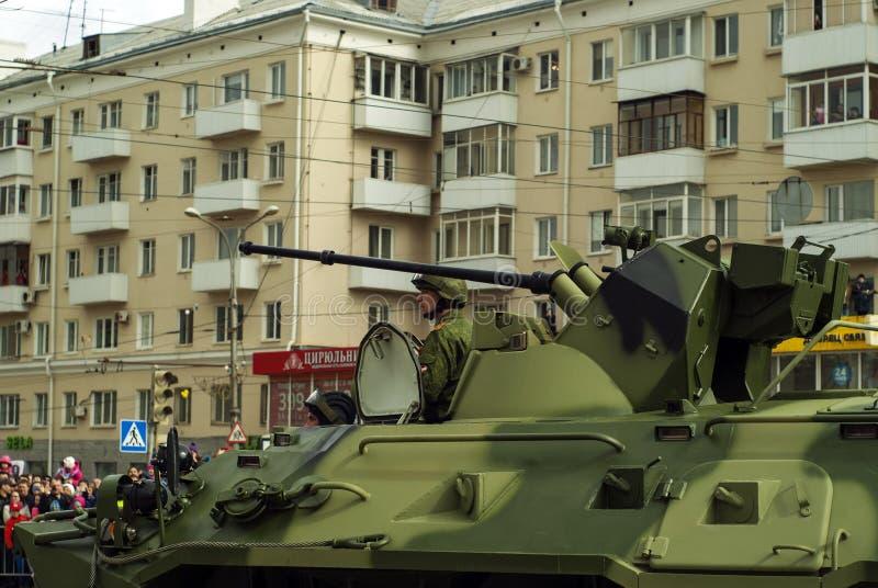 有一个乘员组的装甲运兵车在胜利天游行以后的一条城市街道上 免版税库存照片