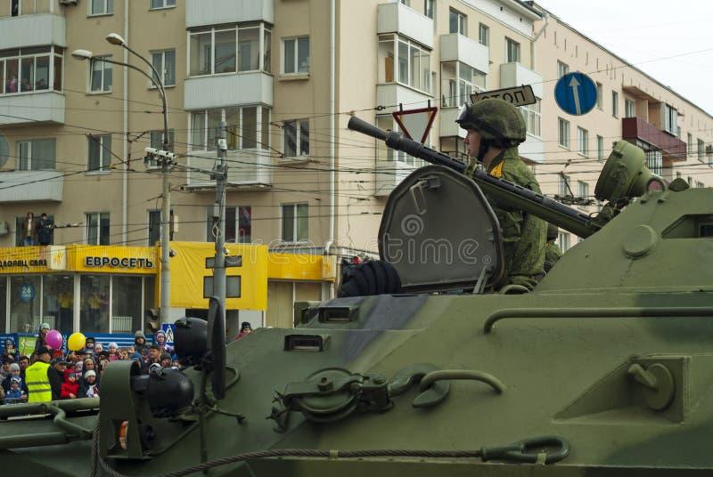 有一个乘员组的装甲运兵车在胜利天游行以后的一条城市街道上 库存照片