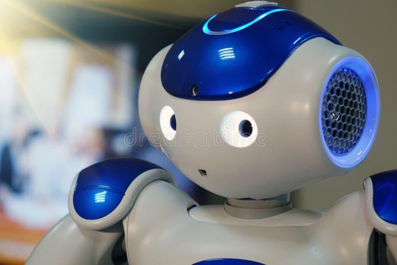 有一个人面和一个有人的特点的身体的一个小机器人 人工智能- AI 蓝白机器人 图库摄影