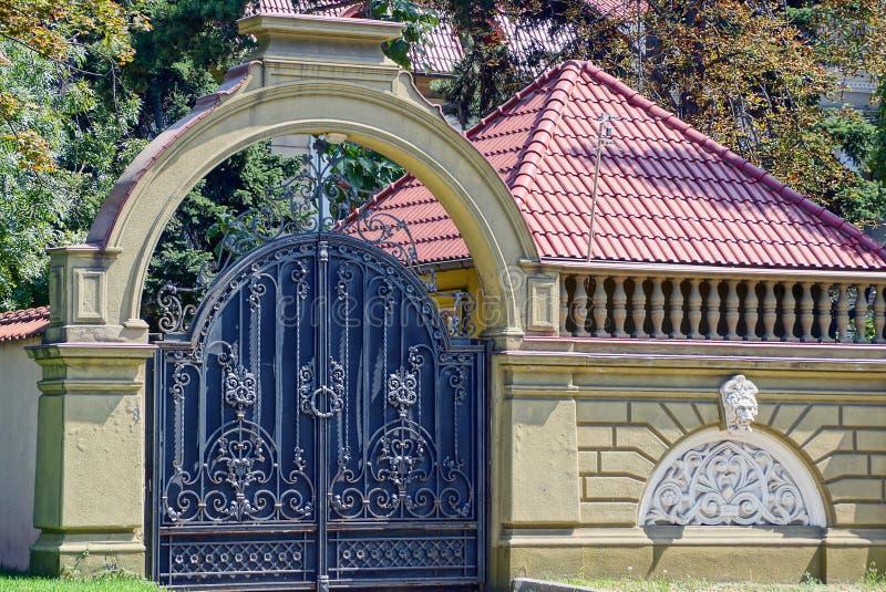 有一个伪造的样式和棕色具体篱芭的大黑铁门 免版税库存图片