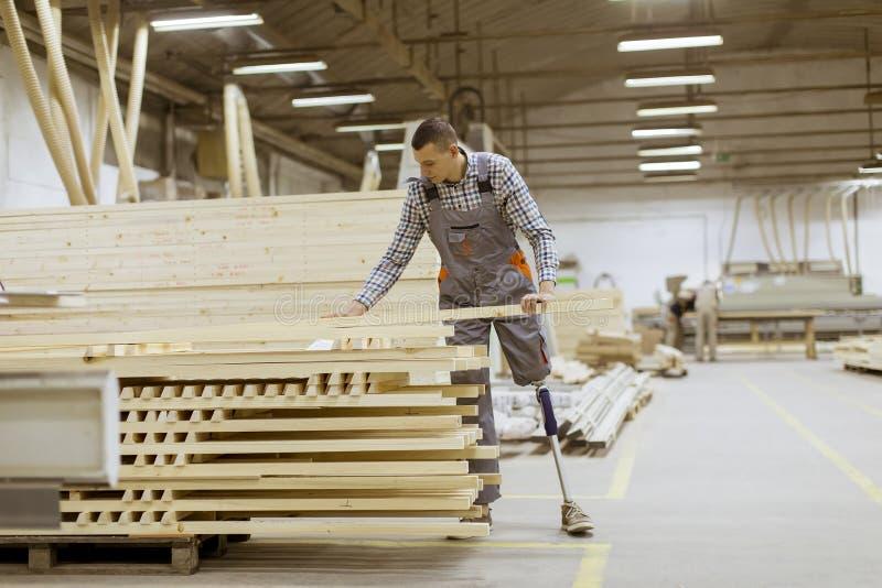 有一个假腿的失去能力的年轻人在家具工厂工作 免版税库存图片
