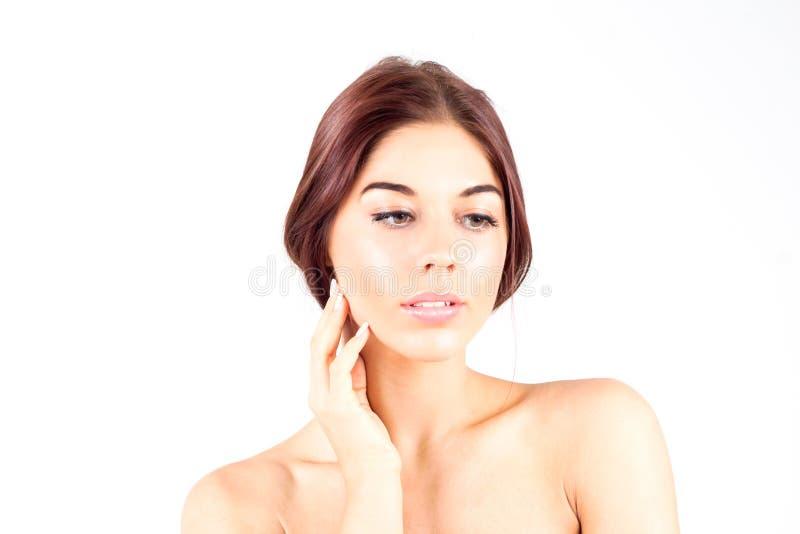有一个光滑和干净的皮肤感人的面颊和看的美丽的妇女下来在白色背景 面部结果 免版税库存图片