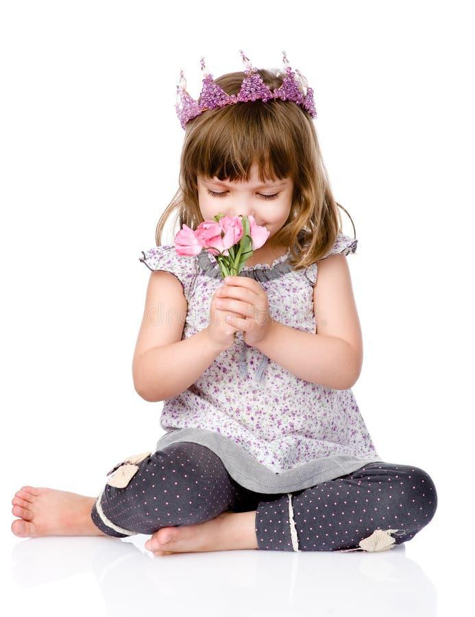 有一个冠的美丽的女孩在花他的顶头嗅花束  免版税库存照片