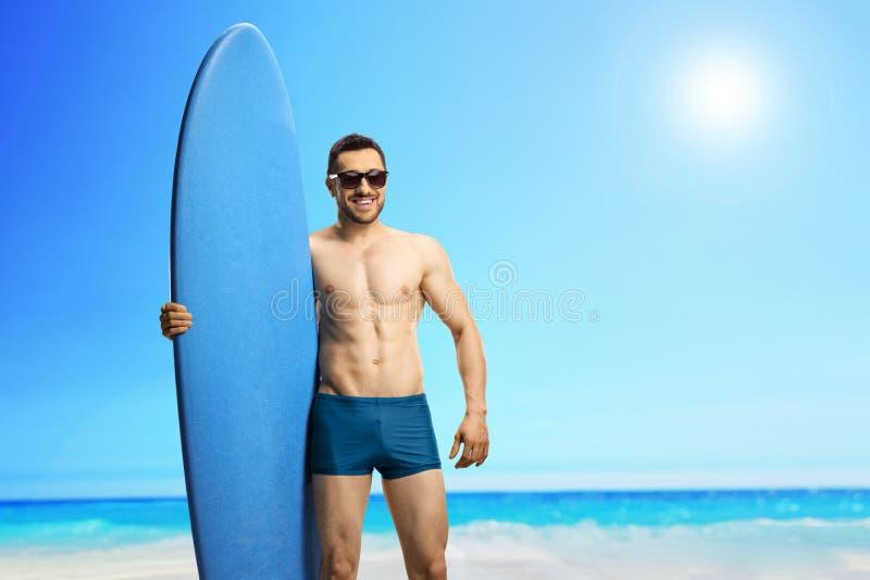 有一个冲浪板的年轻帅哥在海滩 库存照片