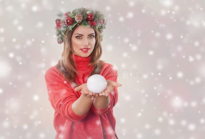 有一个冷杉花圈的一名妇女与在她的头的锥体,在一件红色被编织的毛线衣在她的手上拿着一个雪球 库存照片