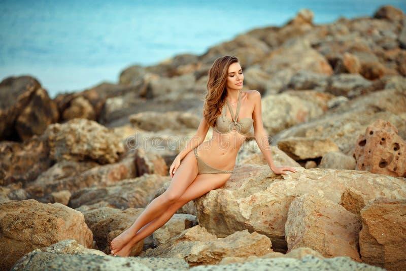 有一个别致的图的美丽的性感的女孩在泳装坐石头反对海 免版税图库摄影
