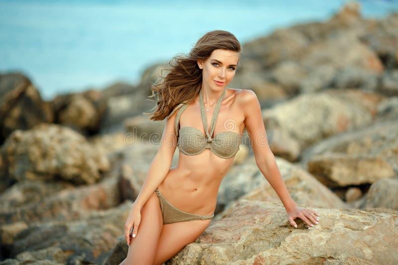 有一个别致的图的美丽的性感的女孩在泳装坐石头反对海 免版税库存图片