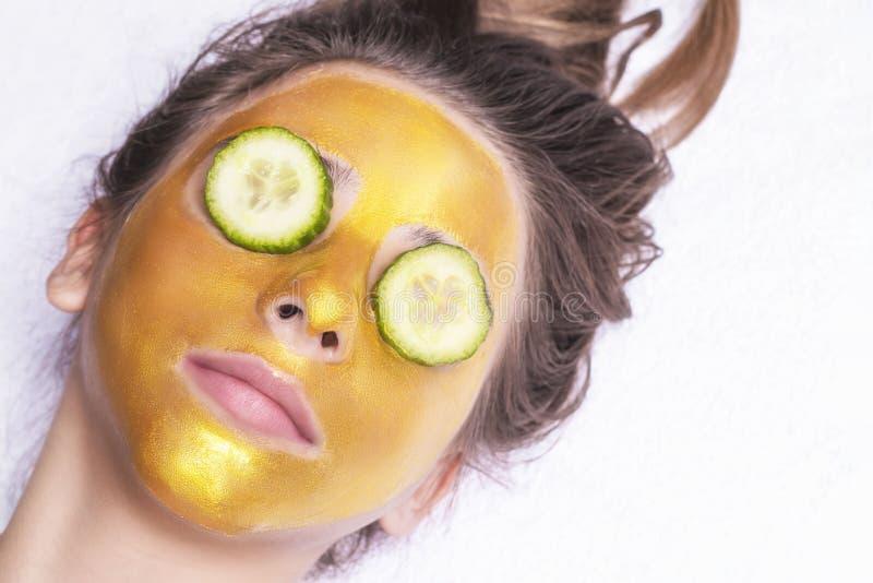 有一个化妆面具的美女在金黄颜色的面孔 r ?? 妇女金面具 美好模型去除 免版税库存照片