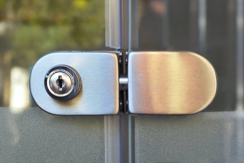 有一个匙孔的金属锁在一个锁着的透明玻璃门,从街道的看法 免版税库存照片
