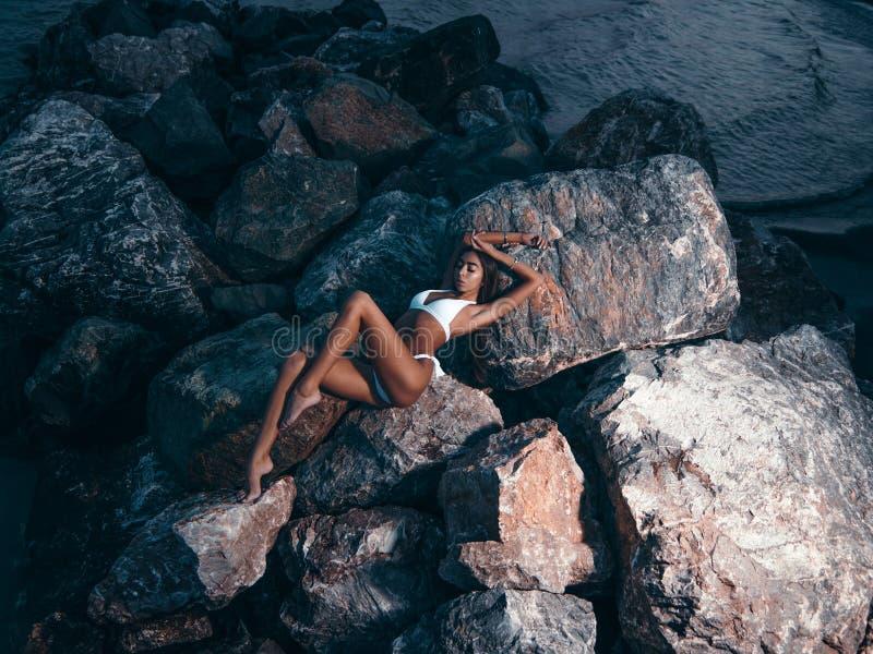 有一个华美的微小的匀称身体的典雅,惊人的年轻女人在比基尼泳装是说谎和摆在岩石在晚上 夏天黑暗的o 免版税库存图片