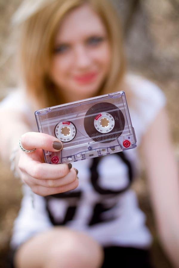 有一个卡式磁带的女孩在她的现有量 图库摄影