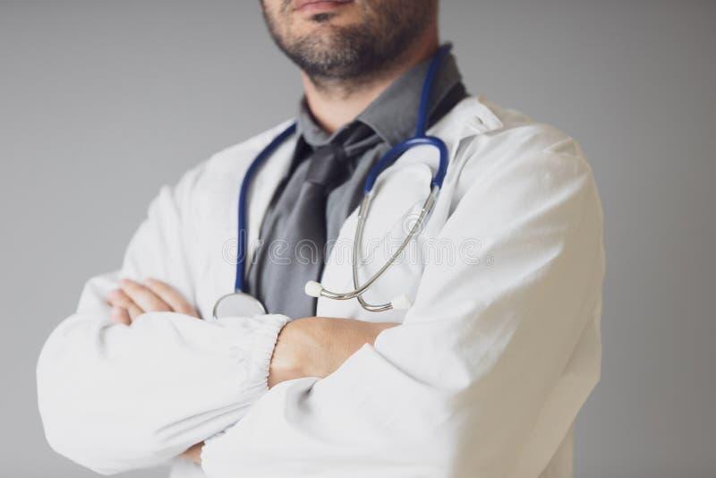 有一个听诊器的一位未认出的医生在脖子上横渡他的胳膊 免版税库存图片