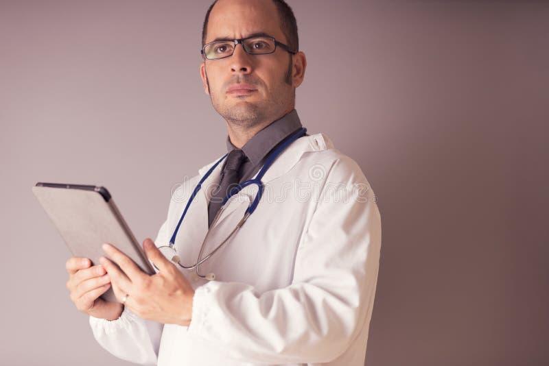 有一个听诊器的医生在他的脖子上看一种片剂 免版税库存图片