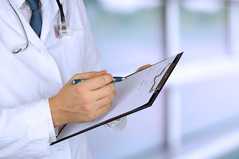 有一个听诊器的年轻医生在他的拿着一个黑文件夹的脖子上 免版税库存照片