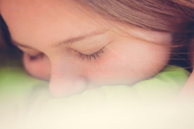 有一个哀伤或疲乏的矮小的女孩的特写镜头画象` s体验缺乏睡眠和她的头下来在浅绿色 图库摄影