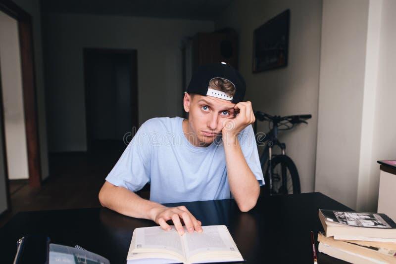 有一个哀伤的表情的年轻人在他的房子里读一本书 免版税库存照片