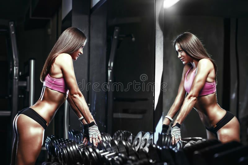 有一个哑铃的健身性感的运动员女孩在健身房 图库摄影