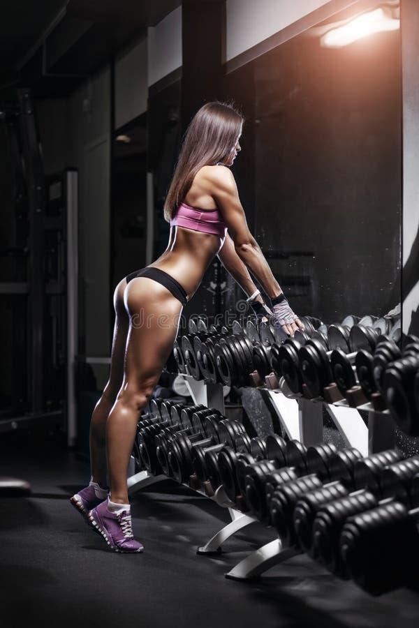 有一个哑铃的性感的运动员在哑铃行的健身房倾斜 免版税库存照片