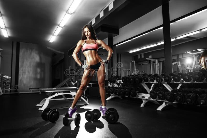 有一个哑铃的性感的运动员女孩在健身房 库存图片