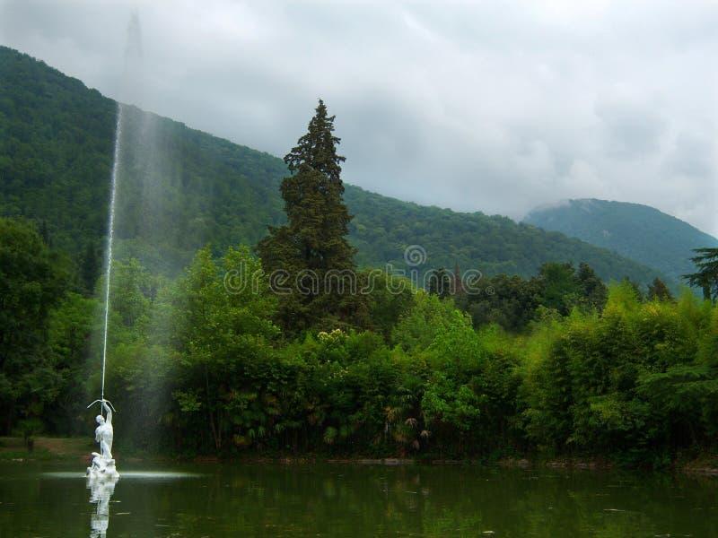 有一个喷泉的绿色池塘在老公园 免版税库存图片