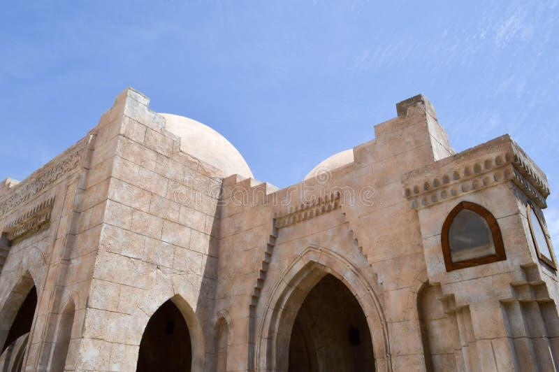 有一个回教伊斯兰教的阿拉伯清真寺的美好的纹理的墙壁由与曲拱,高塔,圆顶a的白色砖建筑学制成 免版税库存图片