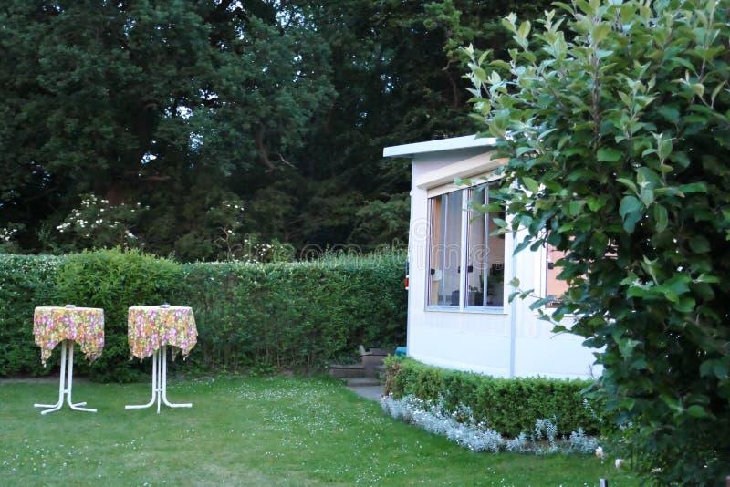 有一个固定的游廊的有蓬卡车由遮篷织品、玻璃可调整窗口和窗帘做成在德国露营地 免版税库存图片