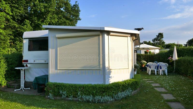 有一个固定的游廊的有蓬卡车由遮篷织品、玻璃可调整窗口和窗帘做成在德国露营地 免版税库存照片