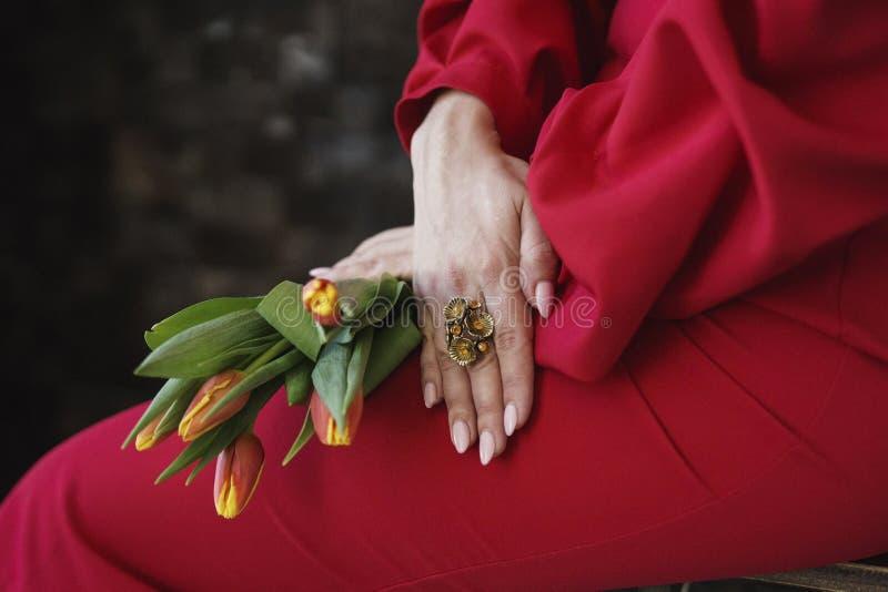 有一个圆环的女孩的手在他的手指和举行郁金香 免版税库存图片