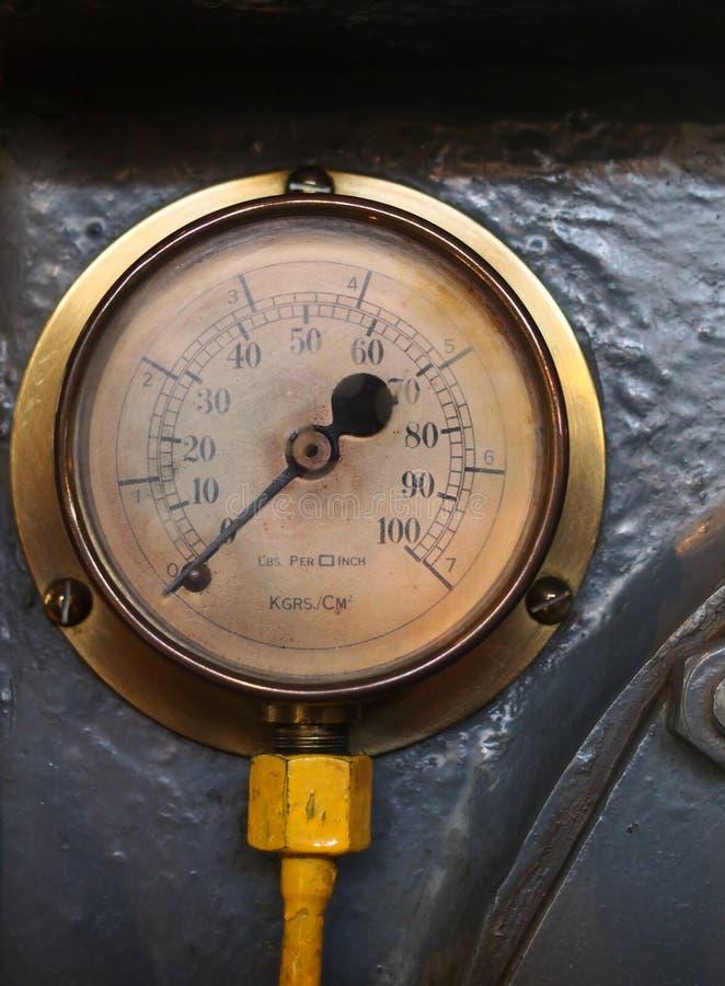 有一个圆的标度的老黄铜压力米与在一个年迈的拨号盘的数字在灰色钢背景 库存照片