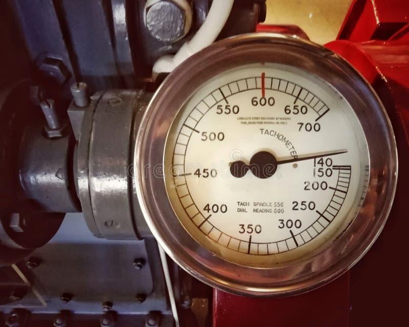有一个圆的测量仪的大老金属车头表有在数字标记的拨号盘的登上在一个大引擎 免版税库存照片