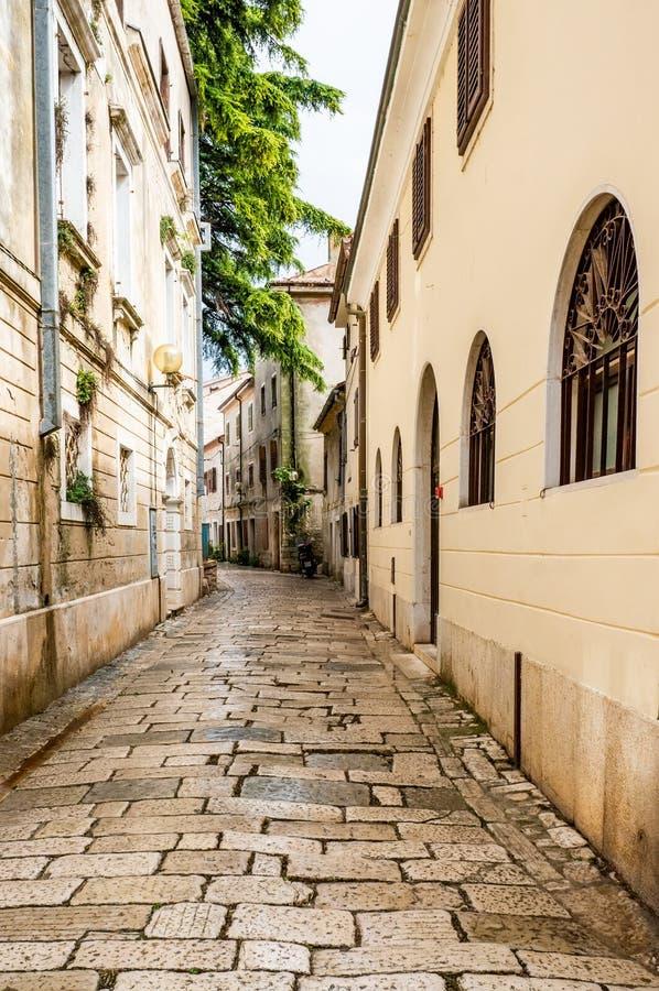 有一个圆石铺砌路面的一条典型的狭窄的欧洲街道 克罗地亚,波雷奇  免版税库存照片
