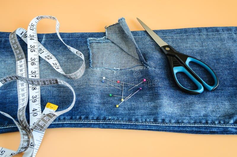 有一个大孔的蓝色牛仔裤在膝盖下的一条裤腿,多色朝向缝合的别针、裁缝磁带和剪刀 库存图片