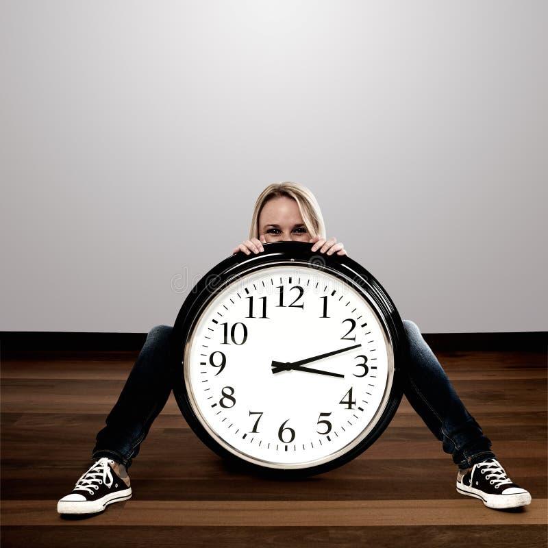 有一个大时钟的妇女: 时间概念 库存图片