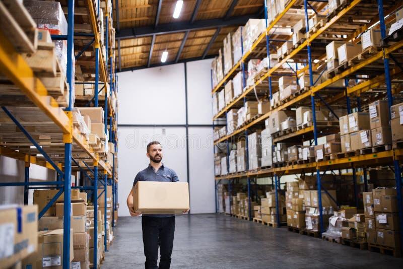 有一个大箱子的男性仓库工作者 免版税库存图片