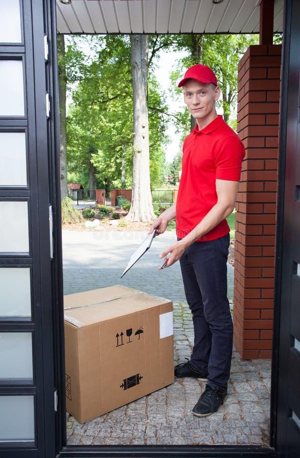 有一个大箱子的送货人 库存照片