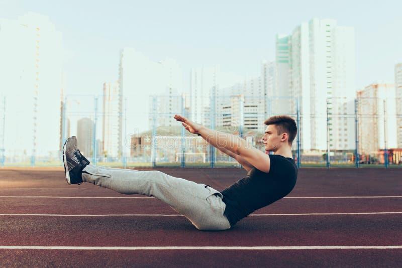 有一个好身体的坚强的人在体育场的早晨 他穿体育衣裳,做锻炼 他看起来紧张 免版税图库摄影