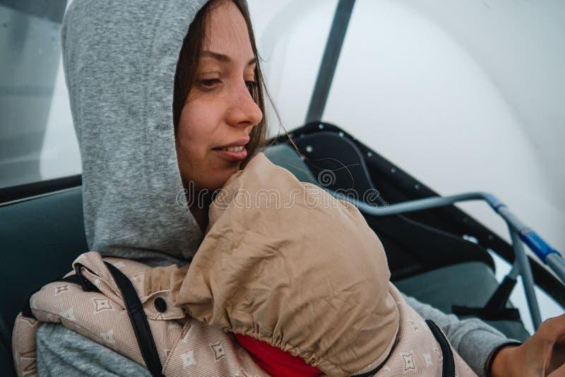 有一个婴孩的年轻母亲背包的 在山的旅行 ? 免版税库存照片